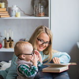 Mother and her son reading book at home Royalty Free Stock Image