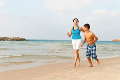 Mother with her son are running on the beach. And having fun Stock Photography