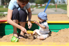 Mother and her son sifted sand. In a sandbox Royalty Free Stock Photos