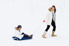 Mother and her son sleigh in snowy winter park Royalty Free Stock Photos