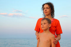 Mother and her son are standing together on beach Stock Images