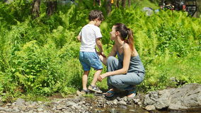 Mother with her son are talking near a stream stock video