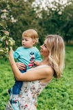 Mother with her son under the apple tree. Mom and son walk in the park outside the city in the evening Royalty Free Stock Photos