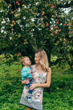 Mother with her son under the apple tree. Mom and son walk in the park outside the city in the evening Stock Photos