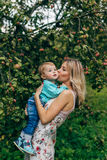 Mother with her son under the apple tree. Mom and son walk in the park outside the city in the evening Stock Photography