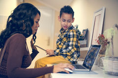 Mother and her son  using technology. African American women and her son using laptop at home Royalty Free Stock Images