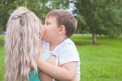 Mother with her son walking outdoor. Child kissing mom Royalty Free Stock Image