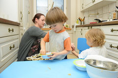 Family cooking. Mother and her sons making muffins together stock image
