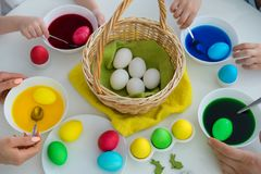 A mother and her sons are painting eggs. Happy family are preparing for Easter. stock photos