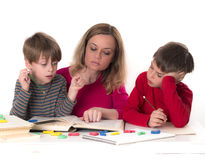 Mother with her sons, reading a book Stock Photos