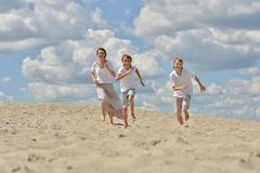 Mother with her sons running on a sand Stock Images