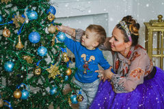 Mother and her sun decorate the new year tree Royalty Free Stock Images