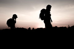 Mother and her tired daughter hiking at sunset Stock Photography