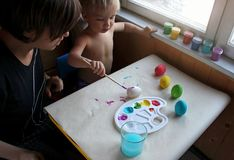 Mother and her toddler blond son dyeing Easter eggs together at home stock images