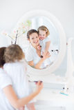 Mother and her toddler daughter applying make up Stock Images