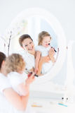 Mother and her toddler daughter applying make up Royalty Free Stock Photos