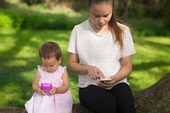 Mother and her toddler daughter both using their own electronic device in the park. Mom and daughter using their different electronic devices while ignoring each Stock Image