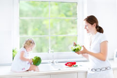 Mother and her toddler daughter cooking healthy salad Royalty Free Stock Image