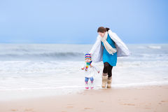 Mother and her toddler daughter running on beach Royalty Free Stock Image