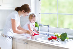 Mother and her toddler daughter washing vegetables Stock Images