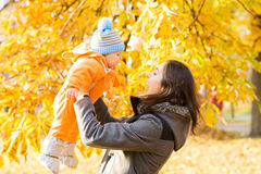 Mother and her toddler son playing in the park. Autumn nature background. Love and family concept Stock Photos