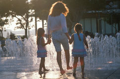 A mother and her twin daughters playing in the water fountains, Los Angeles, CA Stock Photo