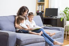 Mother with Her Two Children Reading a Book Together. Family Relationships Concepts. Mother with Her Two Children Reading a Book Together. Sitting on Couch Stock Photos