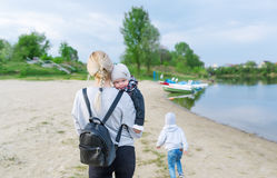 Mother and her two children walk along the picturesque river bank stock photography