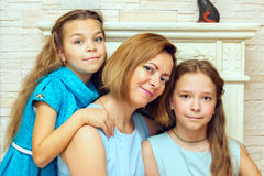 Mother and her two daughters sitting near the fireplace. Royalty Free Stock Images