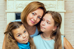 Mother and her two daughters sitting near the fireplace. Stock Photos