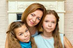 Mother and her two daughters sitting near the fireplace. Stock Images