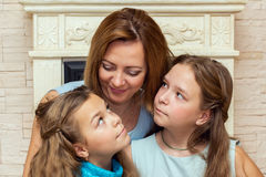 Mother and her two daughters sitting near the fireplace. Stock Photo