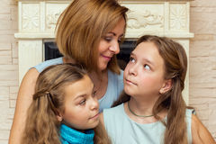 Mother and her two daughters sitting near the fireplace. Royalty Free Stock Photography