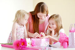 Mother and her two daughters wrapping a gift Stock Images