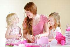Mother and her two daughters wrapping a gift Stock Photos