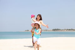 Mother and her two little daughters on the beach Royalty Free Stock Image