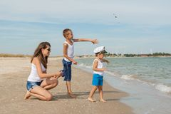 Mother and her two sons having fun on the beach Stock Photography