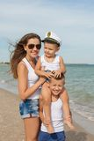 Mother and her two sons having fun on the beach Stock Images