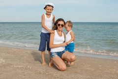 Mother and her two sons having fun on the beach Royalty Free Stock Images