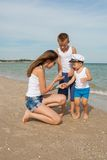 Mother and her two sons having fun on the beach Stock Photo