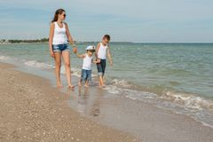 Mother and her two sons having fun on the beach Royalty Free Stock Photos
