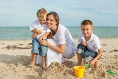 Mother and her two sons having fun on the beach Royalty Free Stock Photography