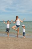 Mother and her two sons having fun on the beach Stock Photos