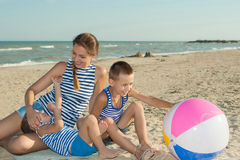 Mother and her two sons having fun on the beach Stock Image