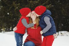 Mother and her two sons having fun in winter in snow forest Royalty Free Stock Photography