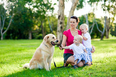 Mother and her two sons in the park with a dog Stock Photography