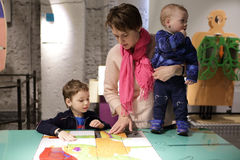 Mother with her two sons playing with puzzle Royalty Free Stock Images