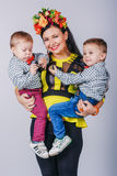 Mother with her two sons in studio. Autumn family look Royalty Free Stock Photography