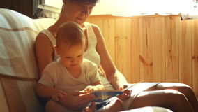 Mother and her two years old baby boy are reading book sitting in armchair in sunny room stock video footage