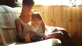 Mother and her two years old baby boy are reading book sitting in armchair in sunny room stock footage
